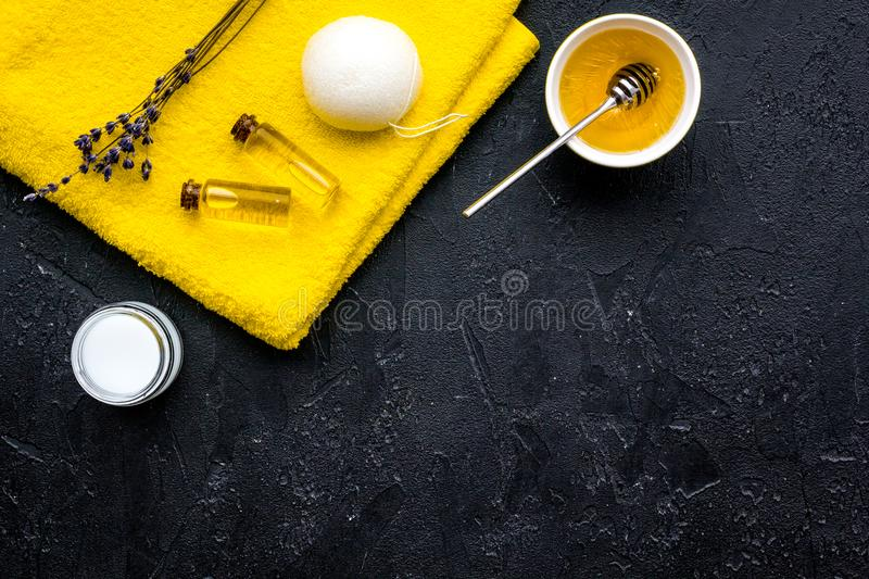 Aromatic theraphy and delicate skin care. Spa set based on honey on black background top view space for text royalty free stock image