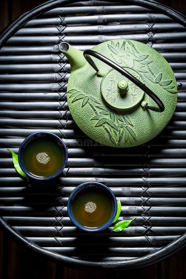 Aromatischer grüner Tee auf schwarzer Tabelle stockbild