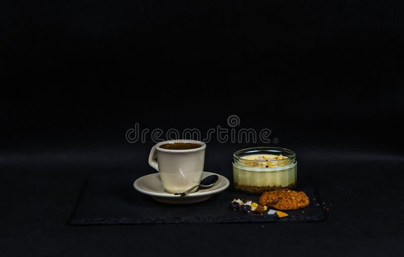 Aromatischer schwarzer Kaffee in einer Schale von sahnigem, von Süßspeise und von Braue stockbild