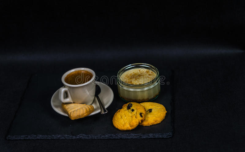 Aromatischer schwarzer Kaffee in einer Schale von sahnigem, von Süßspeise und von zwei stockfotos