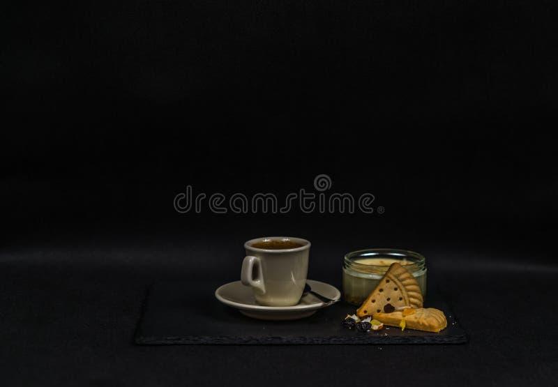 Aromatischer schwarzer Kaffee in einer Schale von sahnigem, von Süßspeise und von zwei lizenzfreie stockbilder