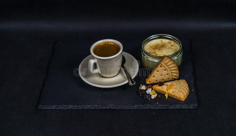 Aromatischer schwarzer Kaffee in einer Schale von sahnigem, von Süßspeise und von zwei lizenzfreies stockbild
