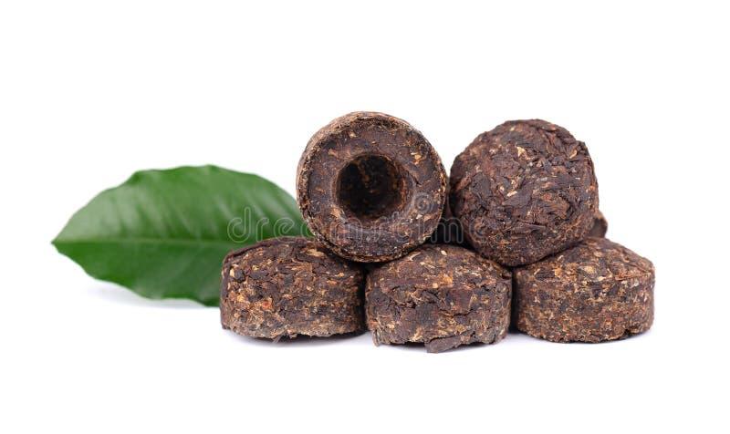 Aromatischer schwarzer Tee PU-erh, lokalisiert auf weißem Hintergrund Abschluss oben Gegoren und zusammengedrückt verlässt in Zie stockfotos