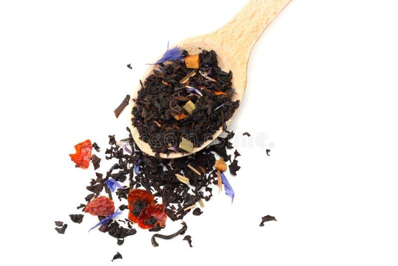 Aromatischer schwarzer trockener Tee mit den Blumenblättern im hölzernen Löffel lokalisiert auf weißem Hintergrund stockfoto