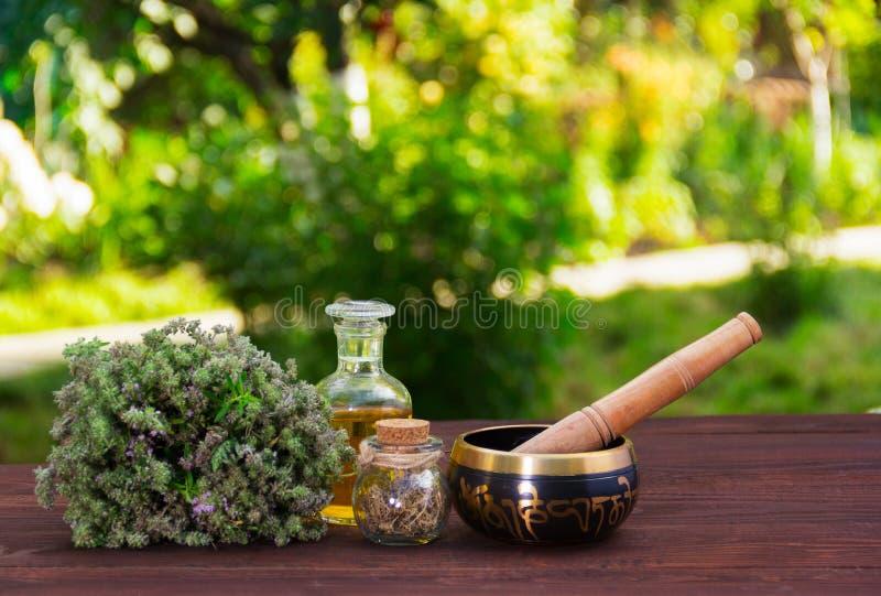 Aromatischer Thymian, ätherische Öle und Gesangschüssel Badekurort und Entspannung Kräuter und Öle auf einem Grün verwischten Hin stockbilder