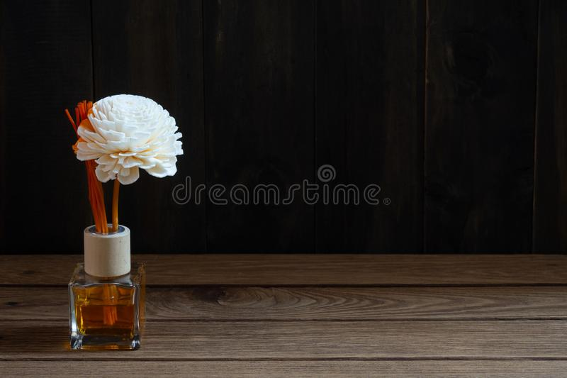 Aromatisches Reederfrischungsmittel, Duft-Diffusor-Satz der Flasche mit Aroma haftet Reeddiffusoren auf dunklem hölzernem Wandhin lizenzfreies stockbild