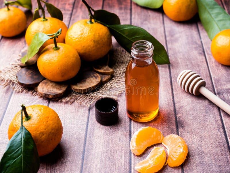 Aromatisches Tangerineöl, mit Tangerinen auf einem hölzernen Hintergrund, selektiver Fokus stockfoto