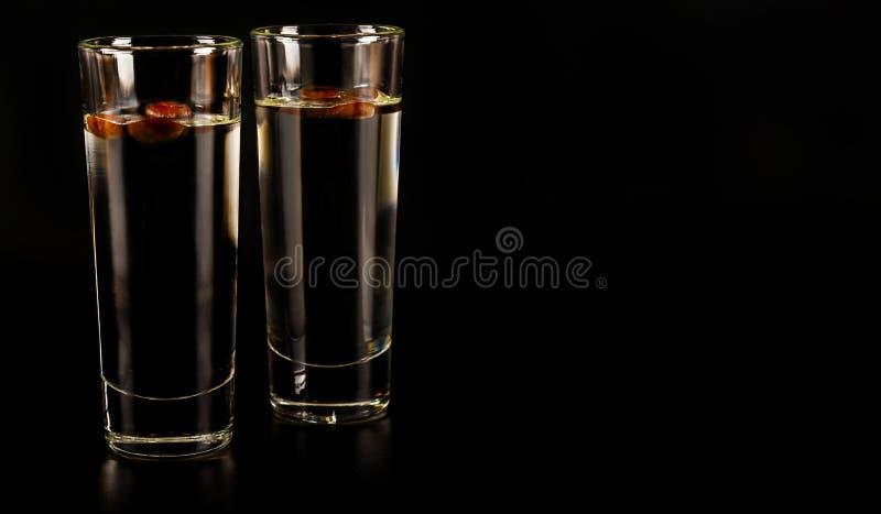 Aromatisk anisalkohol med kaffebönor i ett exponeringsglas, drinkuppsättning arkivbilder