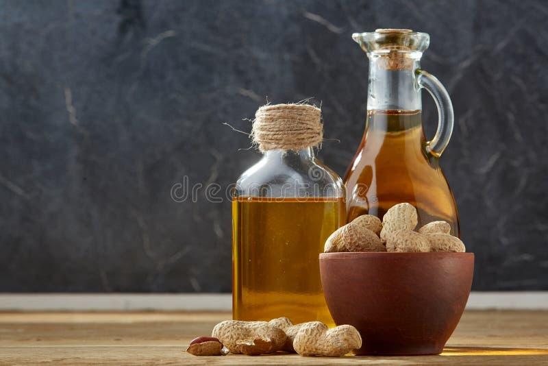 Aromatisk olja i en glass krus och flaska med jordnötter i bunke på trätabellen, närbild royaltyfria bilder