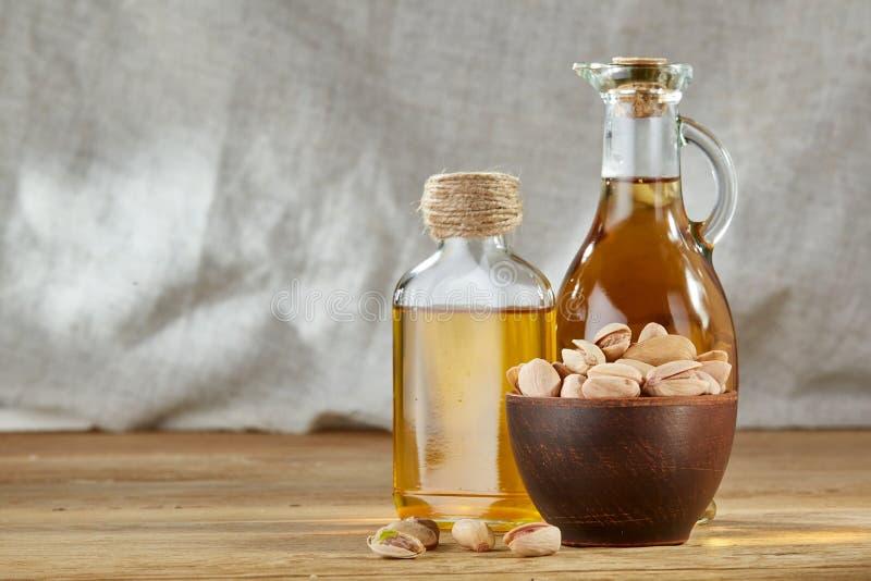 Aromatisk olja i en glass krus och flaska med pistascher i bunke på trätabellen, närbild arkivfoto