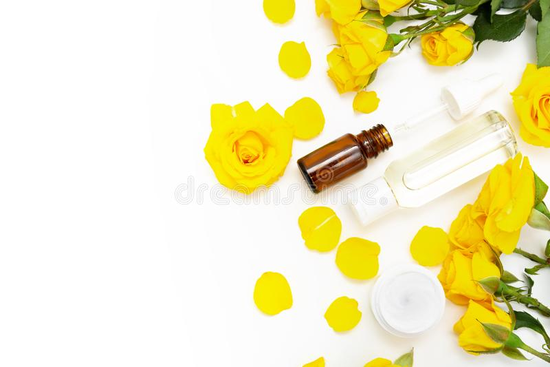 Aromatiska botaniska skönhetsmedel Skincare steg hem- brunnsortbehandling med gula kronblad, blomningen, framsidakräm, flaska av  fotografering för bildbyråer