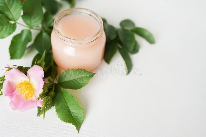 Aromatiska kosmetiska produkter på vitt tabellkopieringsutrymme Glasflaska med extrakten, uppiggningsmedel som inges med blommakr royaltyfria foton