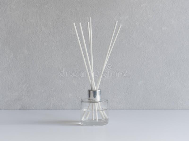 Aromatizador Refrogerador de ar arom?tico em uma garrafa de vidro transparente com juncos brancos em um fundo cinzento fotos de stock