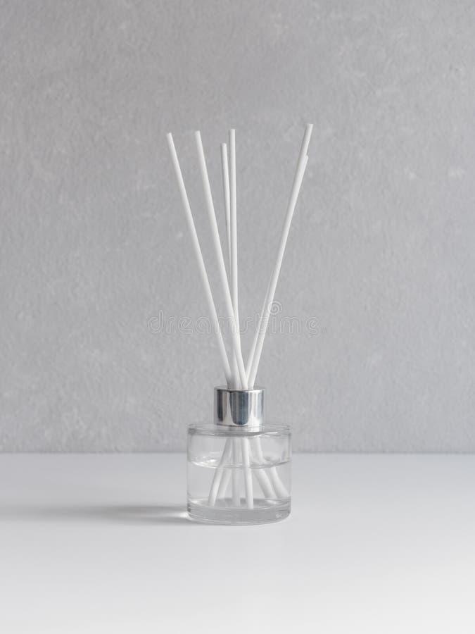 Aromatizador Refrogerador de ar arom?tico em uma garrafa de vidro transparente com juncos brancos em um fundo cinzento foto de stock royalty free