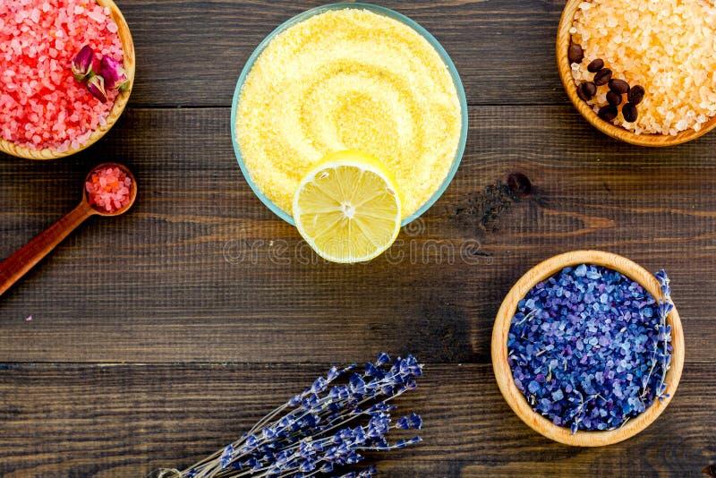 Aromaty kąpielowa sól Cytryna, kawa, wzrastał, lawendowi pobliscy puchary z kolorową kąpielową solą na ciemnego drewnianego tła o zdjęcie stock