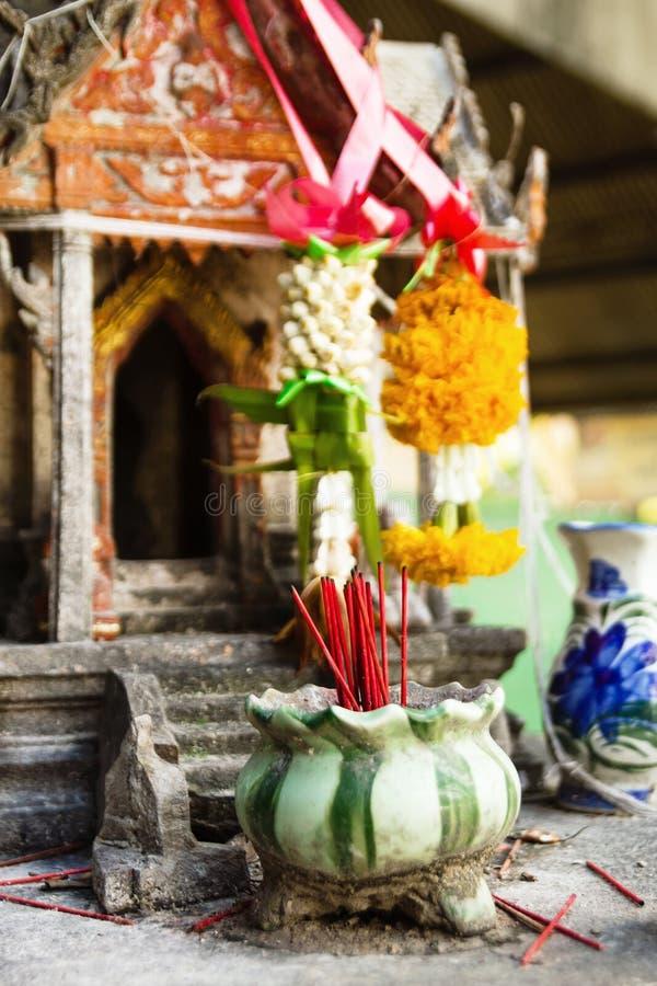 Aromatyczna kadzidłowa czerwień wtyka w glinianym garnku na tle mała świątynia dla ono modli się Buddha fotografia royalty free