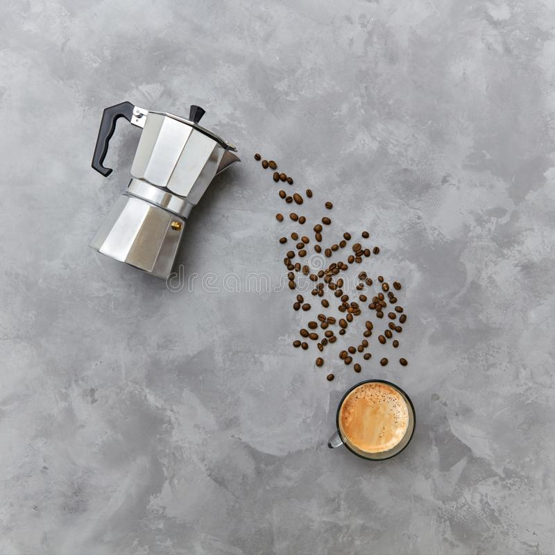 Aromatyczne kawowe fasole w postaci dolewania piją od włoskiego metalu kawowego producenta na szarym tle z kopią fotografia royalty free