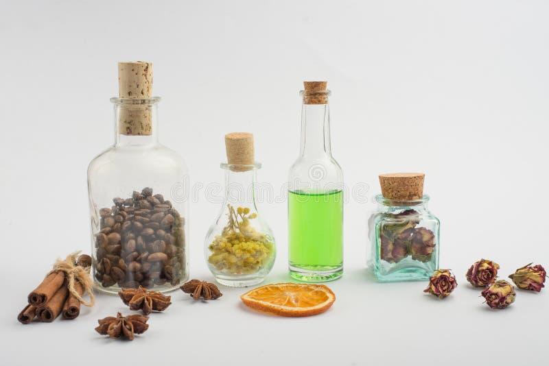 Aromatyczny olej, kawa groszkuje, aromatów ziele w szklanych butelkach na lekkim tle, Pojęcie ciała piękno i opieka fotografia royalty free