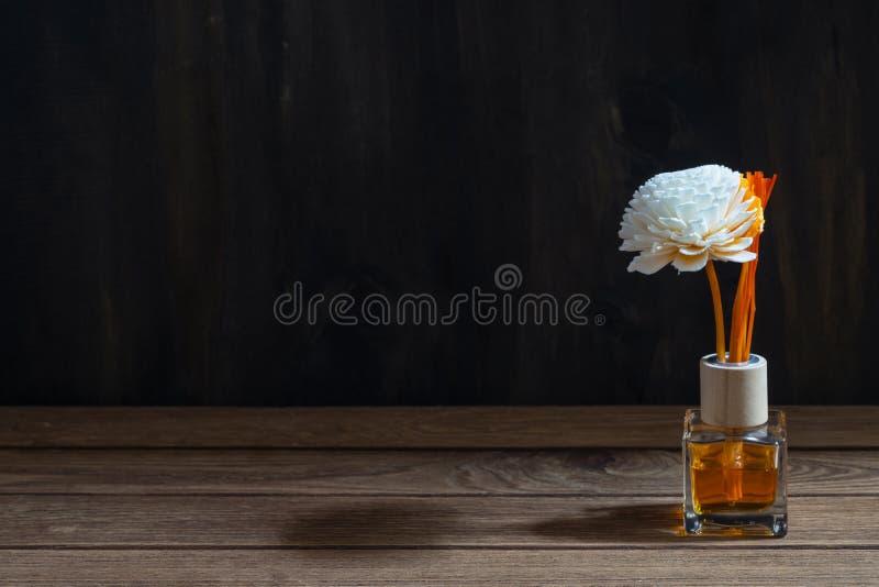 Aromatyczny trzcinowy freshener, woń dyfuzor Ustawiający butelka z aromatów kijów trzcinowymi dyfuzorami na ciemnym drewno ściany fotografia royalty free