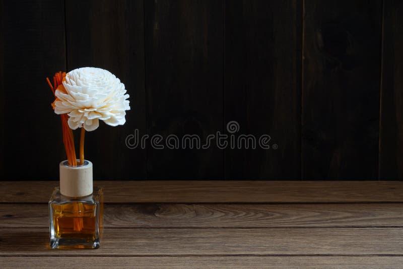Aromatyczny trzcinowy freshener, woń dyfuzor Ustawiający butelka z aromatów kijów trzcinowymi dyfuzorami na ciemnym drewno ściany obraz royalty free