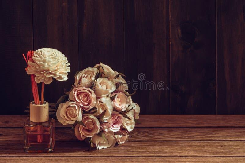 Aromatyczny trzcinowy freshener, woń dyfuzor Ustawiający butelka z aromatów kijów trzcinowymi dyfuzorami z róża kwiatem na drewni zdjęcie stock