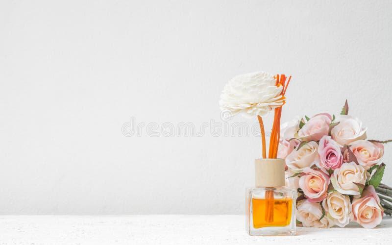 Aromatyczny trzcinowy freshener, woń dyfuzor Ustawiający butelka z aromatów kijów trzcinowymi dyfuzorami z róża kwiatem na biel ś zdjęcie royalty free