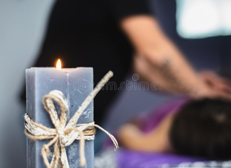 Aromo candle burns in the massage parlor. Focus on the candle. Shallow depth of field stock photo