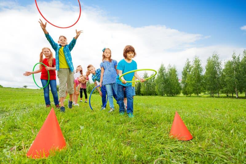 Aros coloridas do lance feliz das crianças em cones fotografia de stock