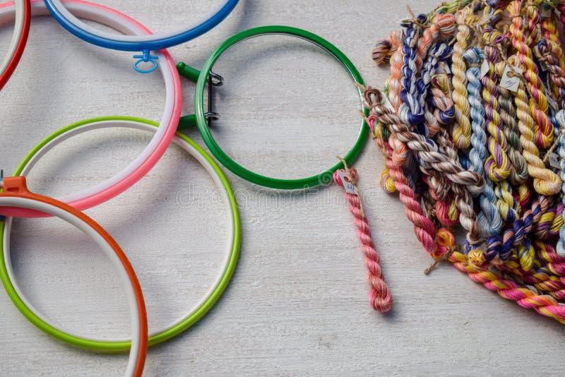 Aros de bordado coloridos para a arte criativa e as linhas de linhas trançadas de floss para o bordado imagens de stock
