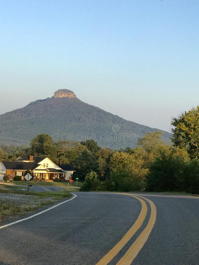 Around the bend in the road. Around and over a hill pops a view of pilot mountain behind a home on a great lot stock images