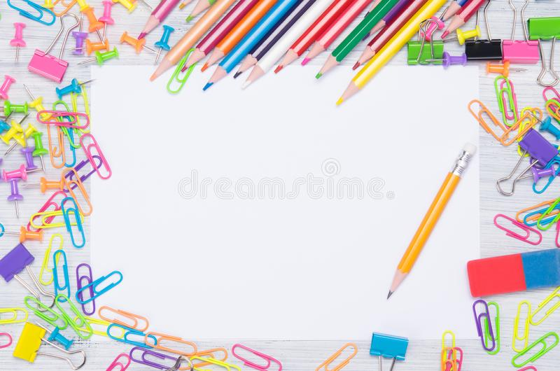 Around the blank sheet of paper scattered colored paper clips, stationery and a simple pencil for writing stock images