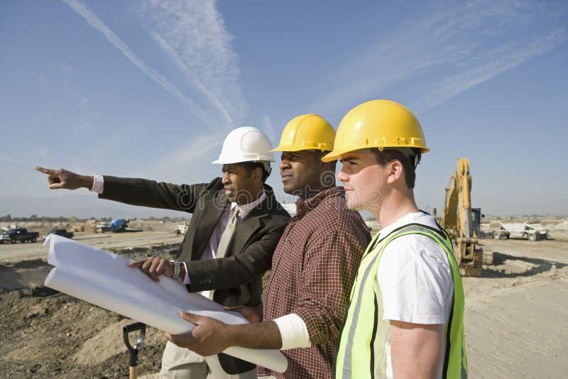 Arpenteur And Construction Workers avec des plans sur le site photos stock