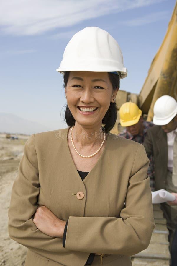 Arpenteur And Construction Workers sur le site photo stock