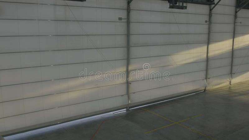 Arplane hangar med stängda dörrar Slutare- eller rulldörren i flygplatshangar öppnar och plan bakgrund fotografering för bildbyråer