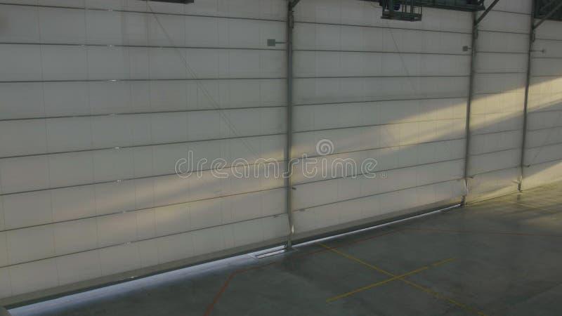 Arplane hangar z drzwiami zamykającymi Żaluzi lub rolownika drzwi w lotniskowym hangarze otwiera i płaski tło obraz stock