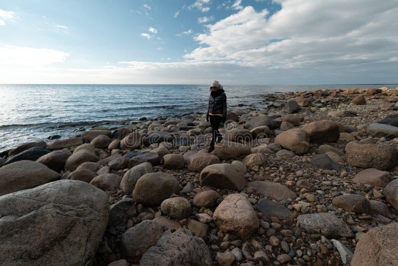 Arqueólogo joven en una playa del canto rodado que busca rocas exóticas en una costa costa de un mar Báltico foto de archivo