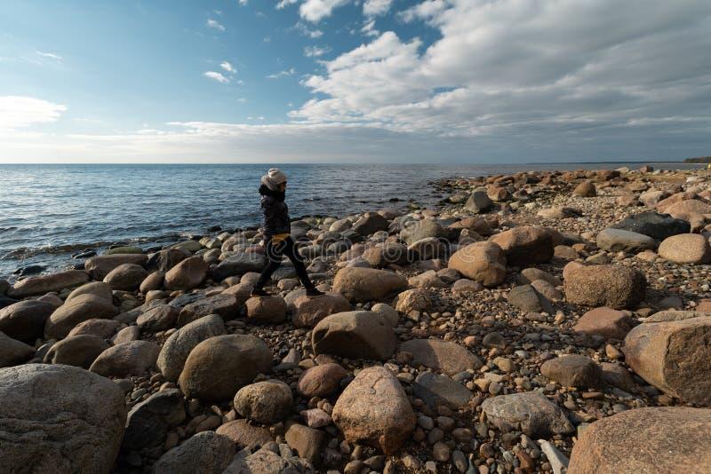Arqueólogo joven en una playa del canto rodado que busca rocas exóticas en una costa costa de un mar Báltico imagenes de archivo