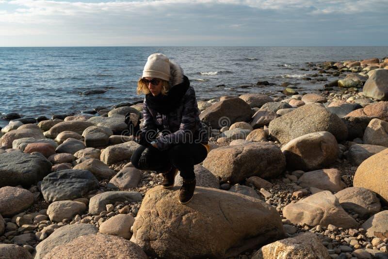 Arqueólogo joven en una playa del canto rodado que busca rocas exóticas en una costa costa de un mar Báltico fotos de archivo