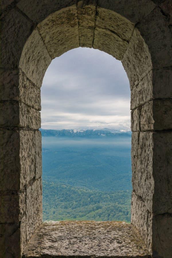 Arqueie a janela na fortaleza, nas montanhas e na opinião de pedra velhas do céu imagem de stock royalty free