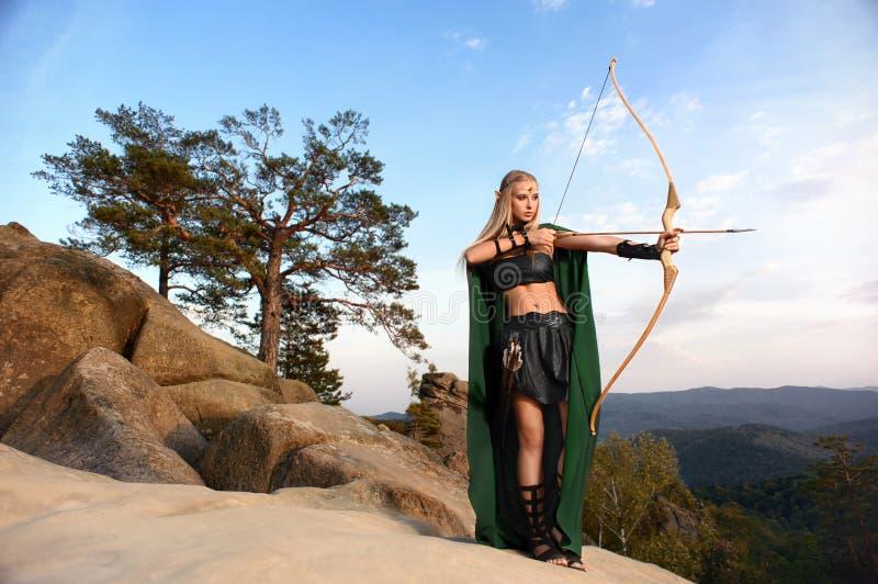 Arqueiro fêmea bonito do duende na caça da floresta com uma curva imagens de stock royalty free