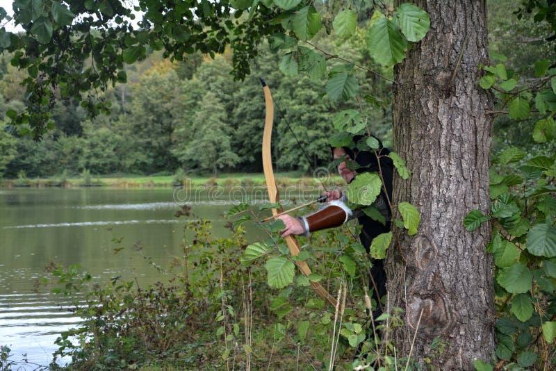 Arqueiro medieval com os suportes pretos da capa escondidos atrás da árvore no lago com curva tensa foto de stock