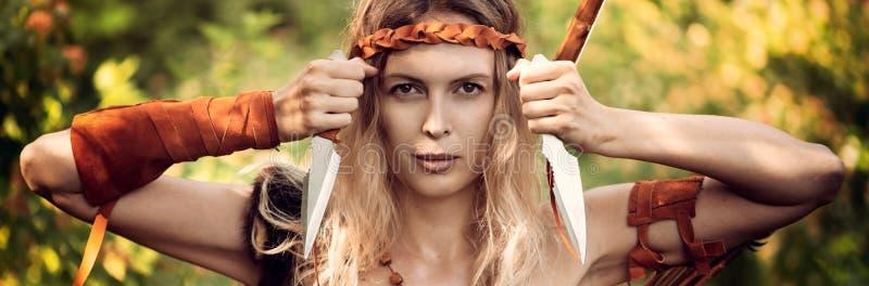 Arquero hermoso de la muchacha con el pelo rubio largo con el arco y el arrowson una parte posterior que sostiene dos brazos frío fotos de archivo