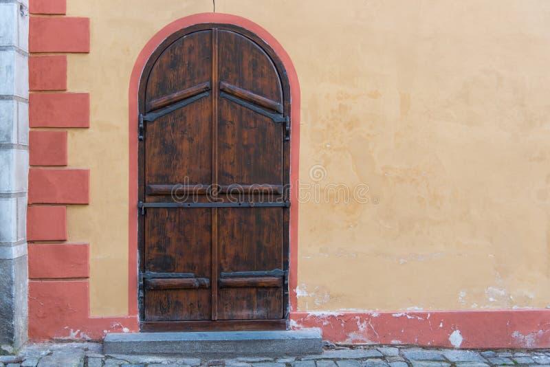 Arquez la vieille porte en bois avec le mur jaune en béton rustique en Europe images libres de droits