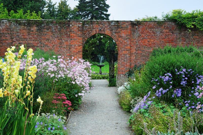 Arquez par un mur dans un jardin aménagé en parc anglais images libres de droits
