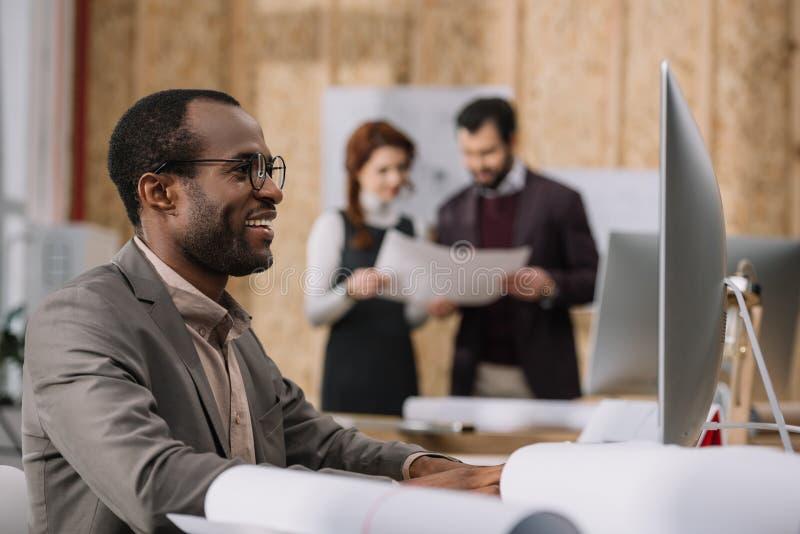 arquitecto afroamericano feliz que trabaja con el ordenador en la oficina moderna mientras que sus colegas imagenes de archivo