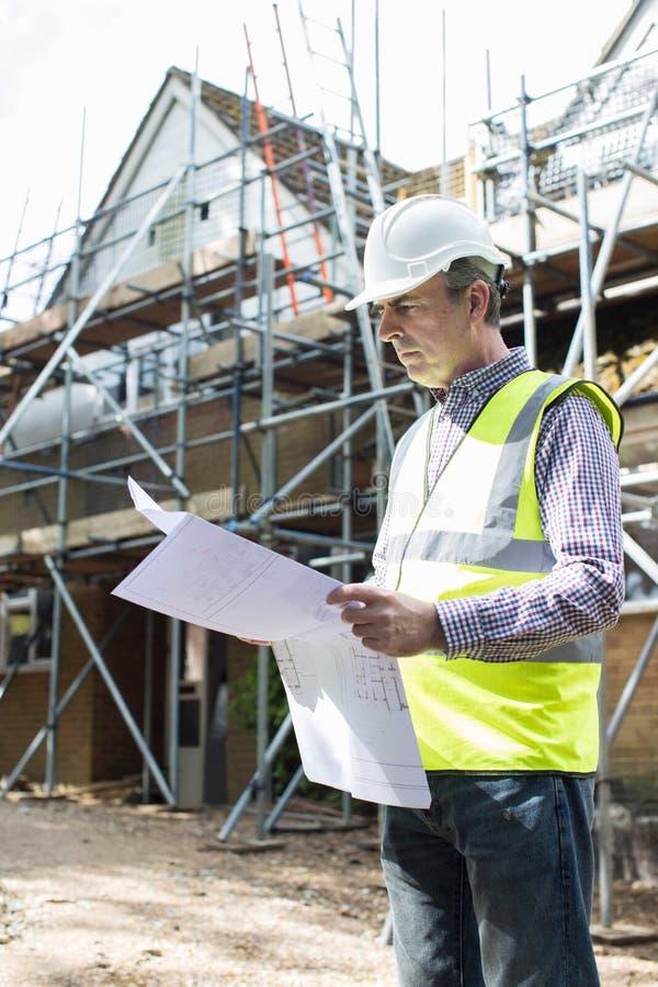 Arquitecto On Building Site que mira planes de la casa imagen de archivo