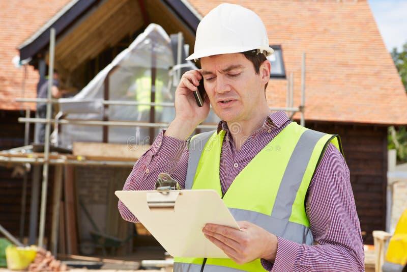 Arquitecto On Building Site que usa el teléfono móvil fotografía de archivo libre de regalías