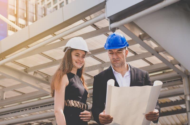 Arquitecto consultivo de sexo masculino de la mujer que trabaja junto mientras que se coloca en solar imágenes de archivo libres de regalías