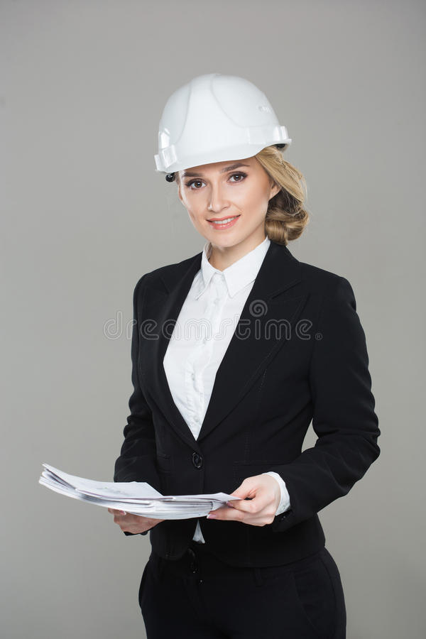 Arquitecto de la mujer con los gráficos Muchacha hermosa en un casco del edificio fotografía de archivo libre de regalías