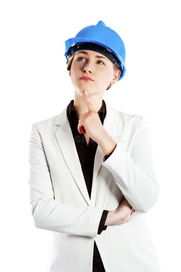 Arquitecto de la mujer de negocios con el casco en su cabeza aislada en el fondo blanco imagenes de archivo
